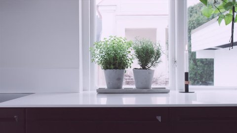 A tracking wide shot inside a modern Scandinavian house. Kitchen and dining area. Slow motion. UltraHD. ProRes444.