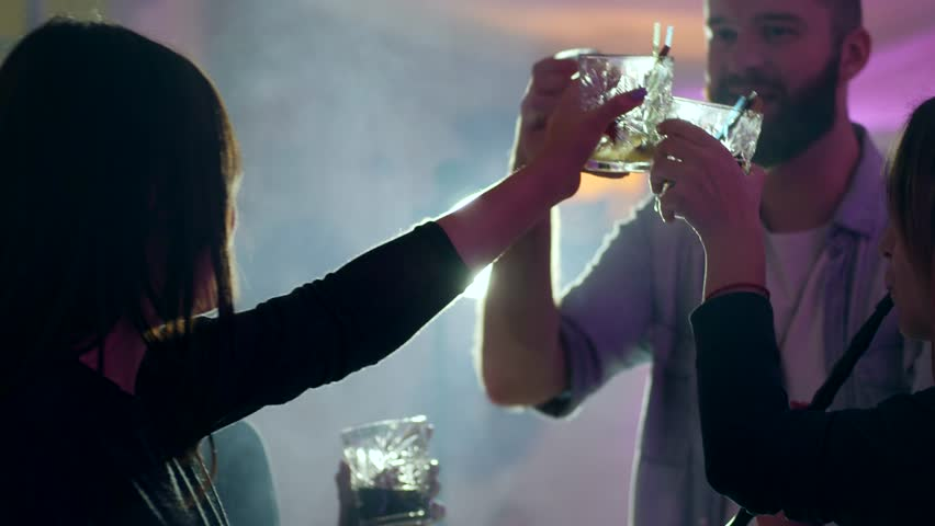 happy friends raise glasses to make a toast with a beverage in hookah smoke at nightclub