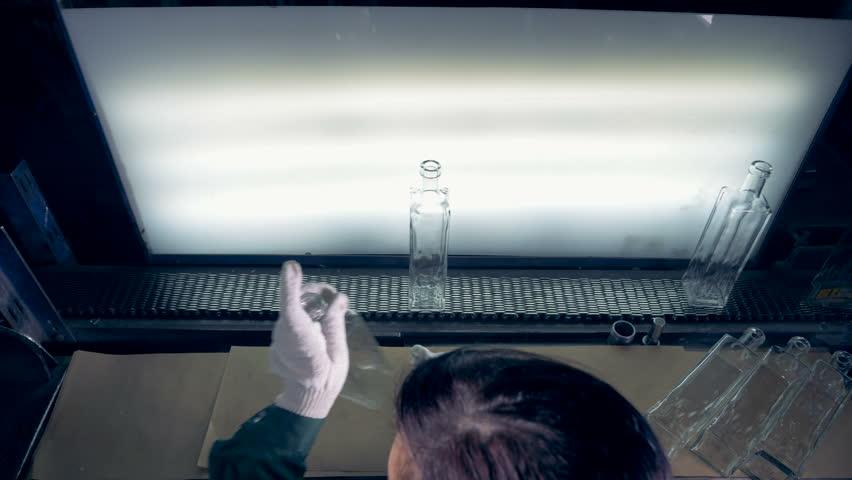 A female worker checks bottles on a conveyor. | Shutterstock HD Video #1010058827