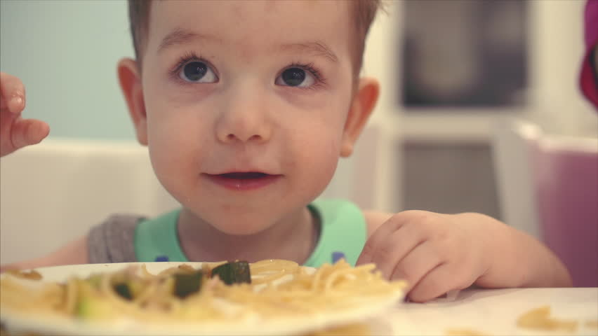 Small child is sitting at a table in a bib and eat his own spaghetti, the baby eats willingly.   Shutterstock HD Video #1010063417