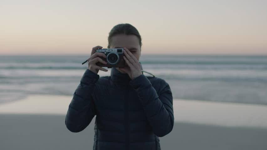 Portrait of young confident woman taking photo using retro camera enjoying calm seaside beach at sunset | Shutterstock HD Video #1010073347