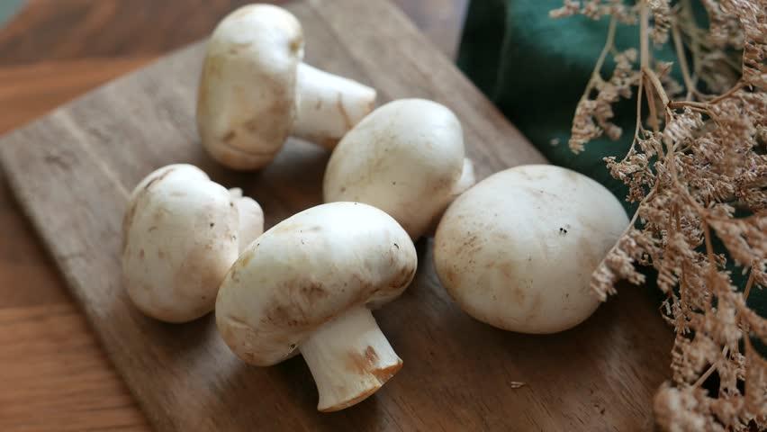 Button mushroom or white mushroom or champignon mushroom. set on table.