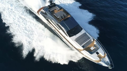 Aerial perpendicular view of a luxury yacht navigating fast.