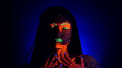 Girl sexy smears and rubs fluorescent paint on her body. Dye glowing under UV black light. Woman with braids in neon light. Night club, party, halloween psychedelic concepts.