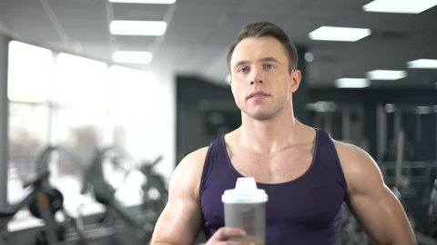 Muscular man drinking protein shake after workout, healthy diet, bodybuilding