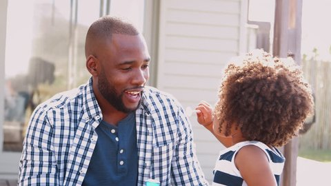Young black girl blowing bubbles with dad outside house