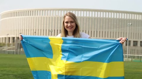 Woman with the flag of Sweden. Woman sporting a fan with the flag of Sweden.