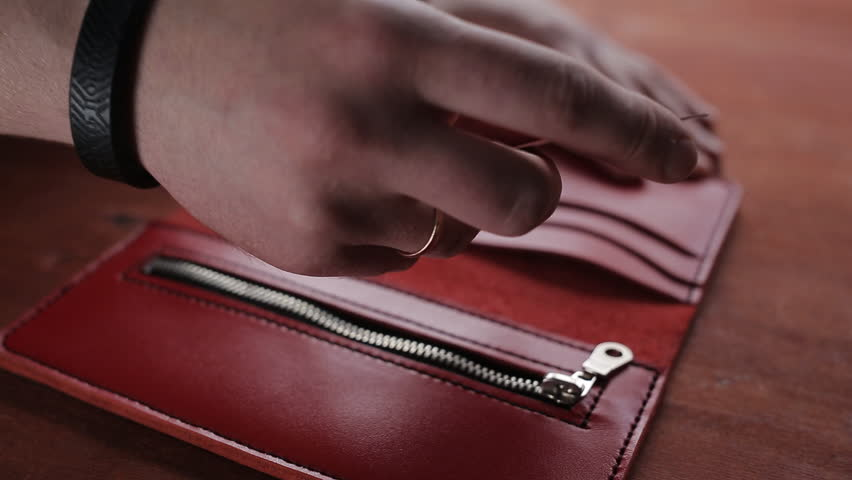 A man lays credit card pockets red wallet