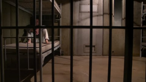 MAN SITS IN AN EMPTY JAIL CELL, MODEL RELEASE
