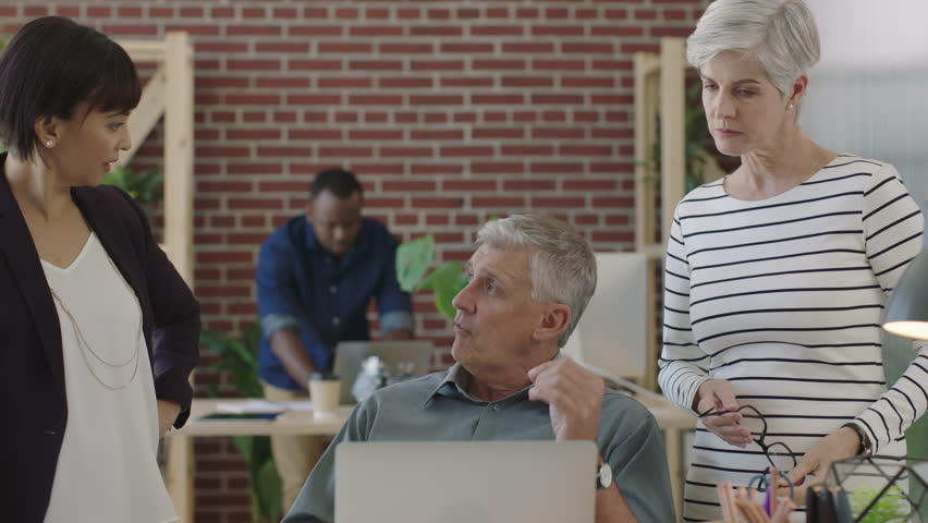 Mature diverse business team using computer brainstorming creative strategy for start up company collaborating in modern office workspace | Shutterstock HD Video #1010156777