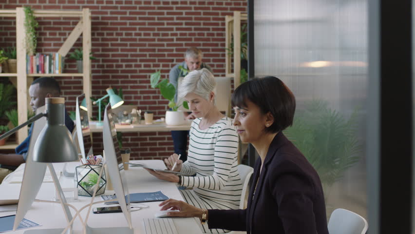 Mature mixed race business woman using computer in modern office young female intern showing graph research diverse team collaborating in workspace | Shutterstock HD Video #1010157617