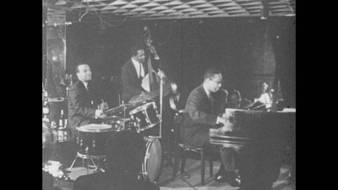 1960s: Jazz trio plays instruments on small stage. The Billy Taylor Trio plays for audience.