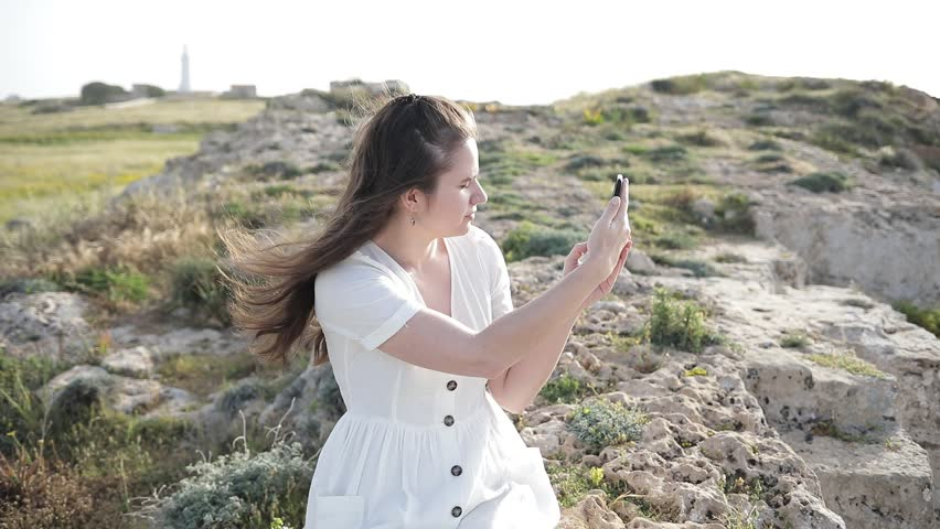 Young girl does photo near to the blue sea sitting on a mountain Woman Watching Sunset. Takes Panorama Photos On Phone. Hair in the Wind | Shutterstock HD Video #1010172167