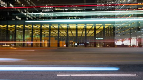 Cars travelling down Bay street in downtown Toronto, Ontario Canada. Long exposure light trails show a fast paced city at night. Futuristic and modern architecture in the background.