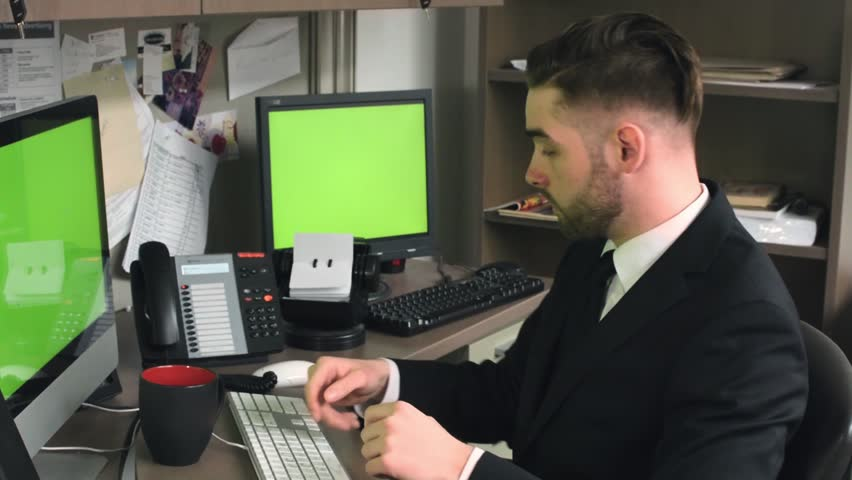 Millennial male office worker happily picks up the telephone as it rings and starts to talk with chroma keyed computer monitors | Shutterstock HD Video #1010175467
