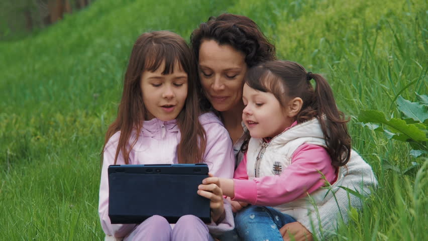 Family with a tablet on the nature. Children with mom in the park with a gadget. | Shutterstock HD Video #1010176007