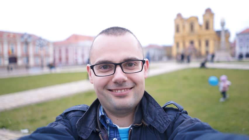 Man recording selfie video vlog at Timisoara. Young Caucasian man stands at a city square, records video vlog, camera point of view. Shot at city of Timisoara, Romania.