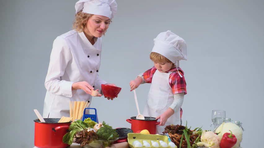 Cute little boy and his beautiful mother smiling while cooking in kitchen. Young family cooking food in kitchen. Young mother and son cooking meal together.   Shutterstock HD Video #1010186627