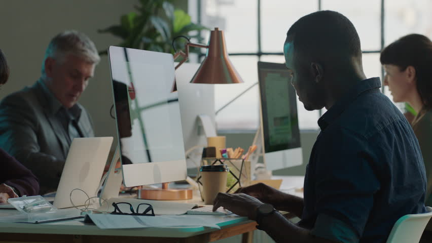 Diverse small business team working late using computer technology in creative office workspace | Shutterstock HD Video #1010189657