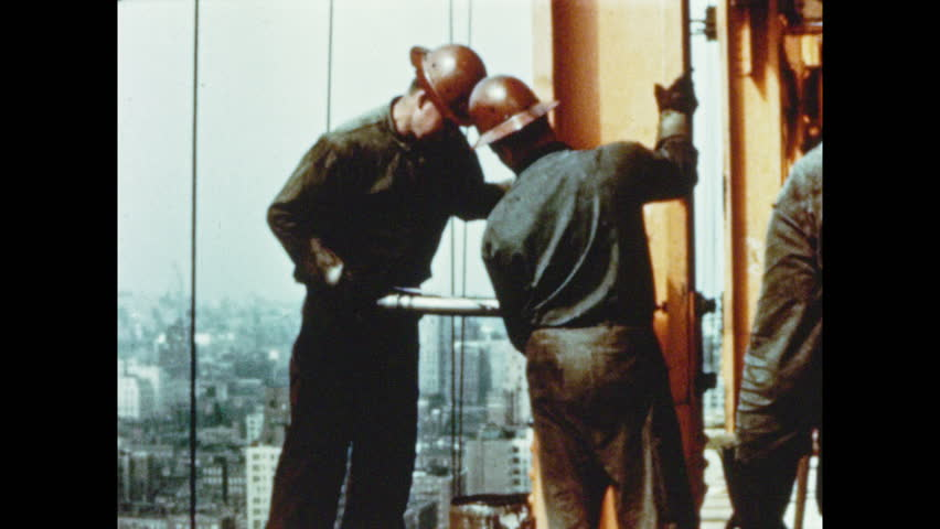 1950s: Men attach beams to column with air hammer. Illustrated picture of skyscraper construction progress. Skyscraper construction frame stands near river in city.