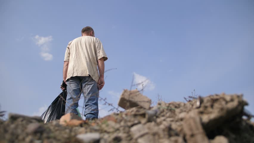 Low angle view of male in dirty clothes standing on top of garbage heap at dump landfill site holding trash bin bags in hand. Blue sky on the background. Environmental problems and pollution concept.