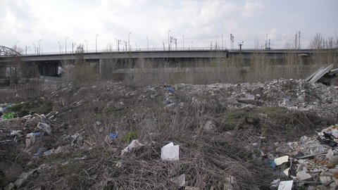Panoramic view of illegal garbage dump within city borders. Piles of trash at landfill site. Unlawful contamination with plastic and construction waste. Environmental problems and pollution concept.