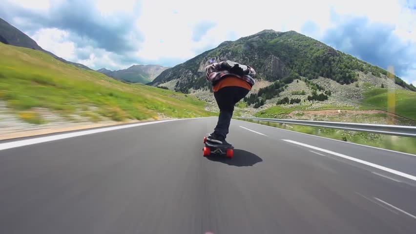 Downhill road in mountain landscape professional skater skating longboard fast in first person pov