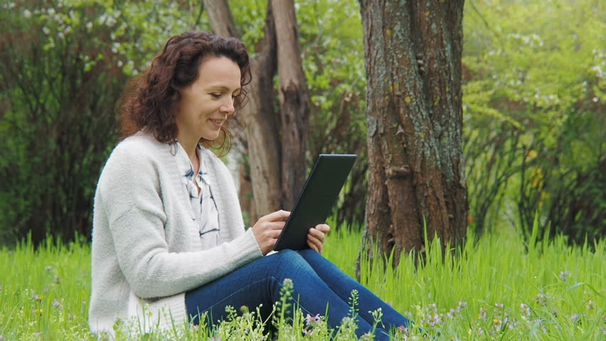 Woman with a tablet on the nature | Shutterstock HD Video #1010224157