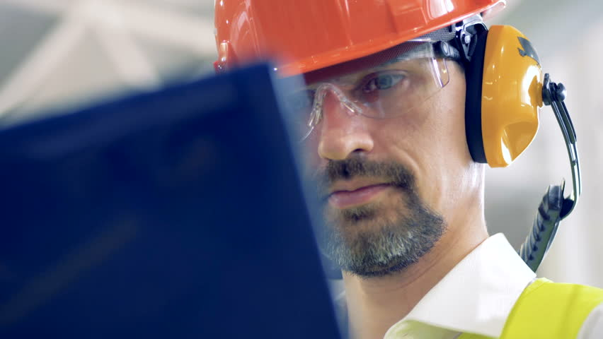 A man in hard hat works on his laptop at a warehouse, close up. | Shutterstock HD Video #1010228057