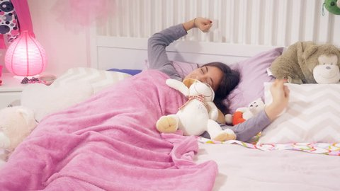 Young woman sleeping in bed with toy plush waking up in the morning