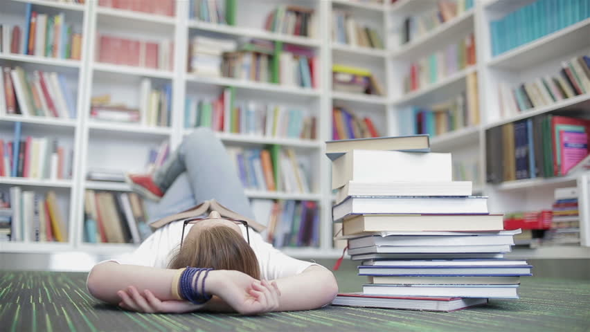 smart looking famale student girl in collage school library reading book
