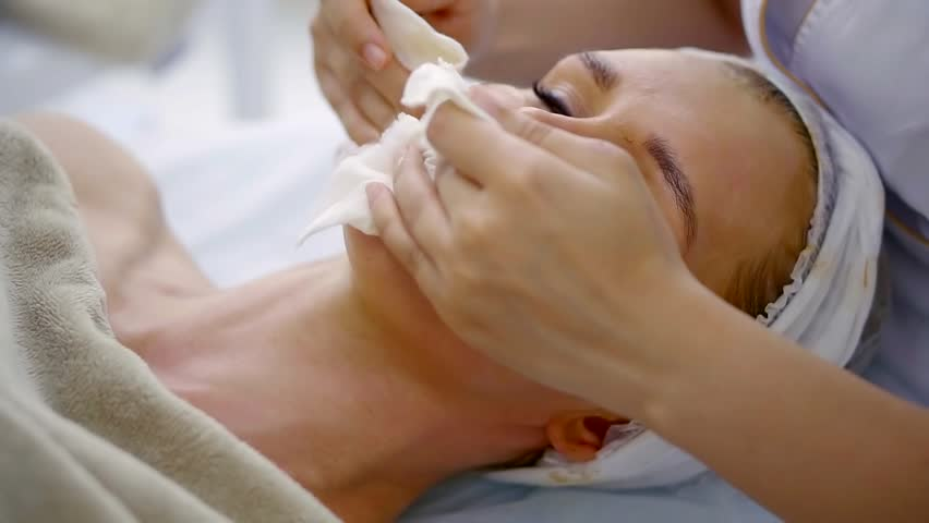 Beautician is removing cosmetic mask from facial skin of woman lying on a table, using napkins   Shutterstock HD Video #1010268977