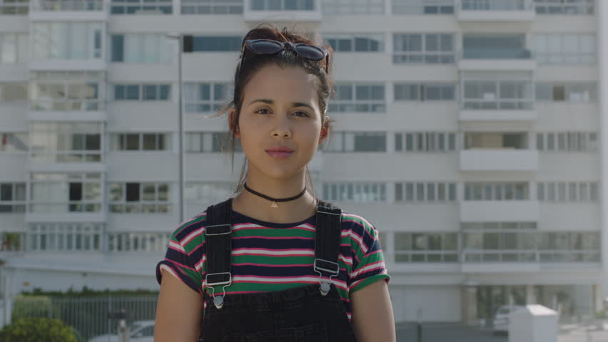 Close up portrait of beautiful young hispanic woman student breathing relaxed looking at camera enjoying sunny urban day in city real people series | Shutterstock HD Video #1010276777
