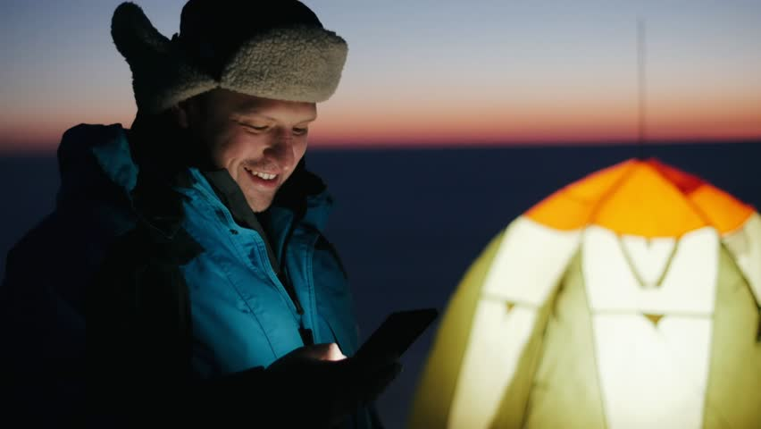Fisherman using mobile phone on background winter tent and beautiful evening sunset in sky over frozen lake. Man angler with smartphone on background tent for winter fishing