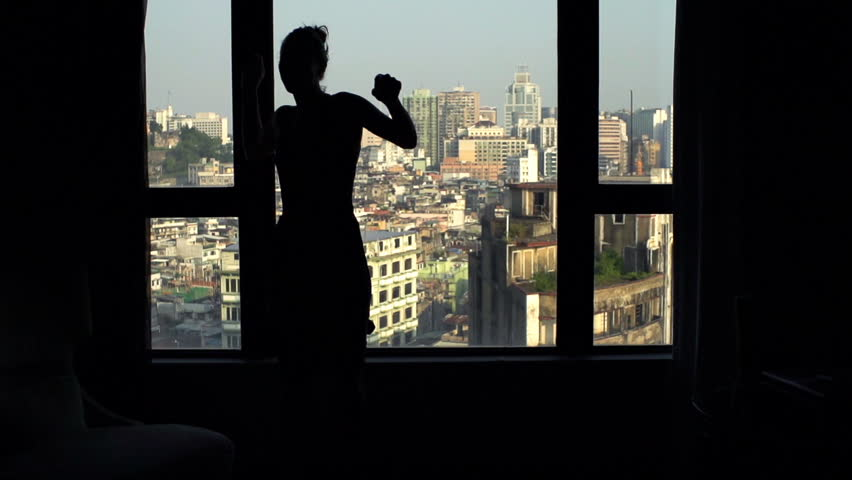Silhouette of happy woman dancing by window at home  #1010289947