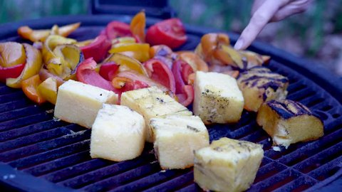 As slider to the right someone flips polenta over on the grill with roasted peppers in the distance.