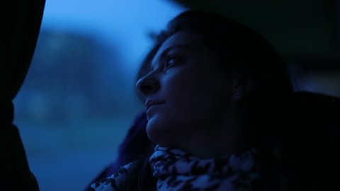 Woman traveling by bus in twilight hours of the night. Girl looking out window in blue tone while on a bus