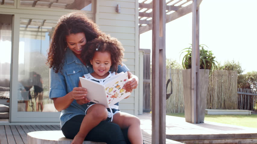 Young black girl reading book sitting on mum's knee outdoors | Shutterstock HD Video #1010328527