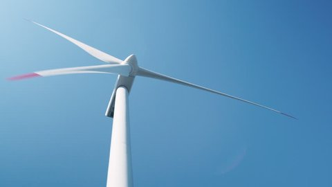 Alternative energy sources. Large rotating wind turbine blades against the blue sky on a wind farm close-up. Smooth motion