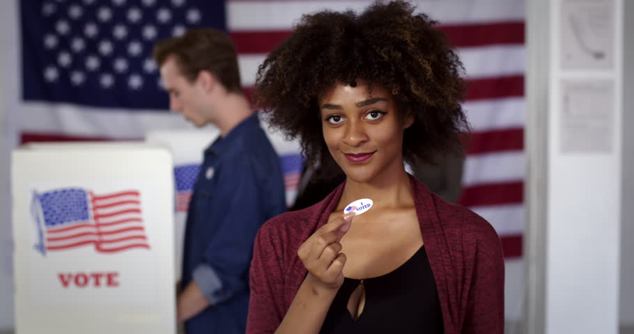 """MCU Young mixed race American woman puts on """"I Voted"""" sticker and gives thumbs up, standing proud in front of polling booths with US flag. Fluid head tripod, real-time 4K 