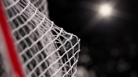 Hockey puck flies into the net on a black background with photo flashes. The movement at the beginning is accelerated then slowly. Beautiful close-up (4k, 3840x2160, ultra high definition)