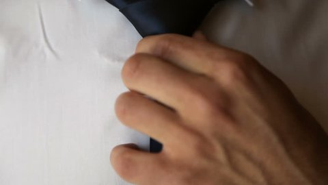 Close-up of man in white shirt correcting his tie.