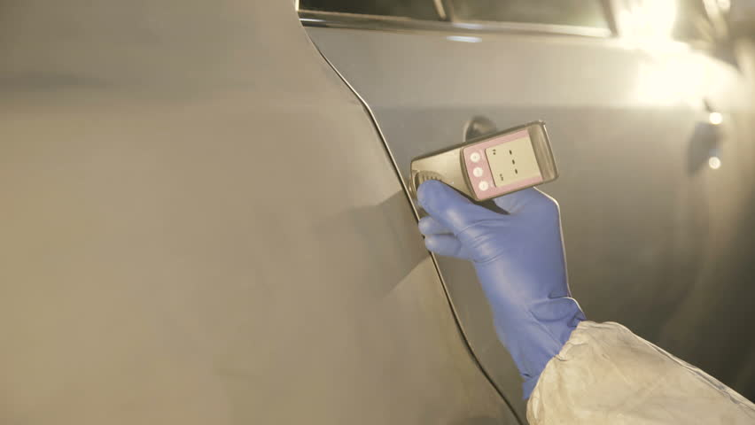 View of measuring a thickness of primer on a car surface using a thickness gauge 4K.