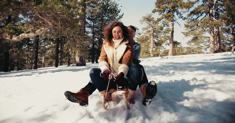 Young couple having fun riding sleigh down snow covered mountain hill in forest