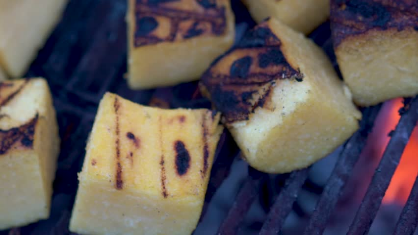 Extreme closeup of polenta on a hot grill while the camera slides to the left.