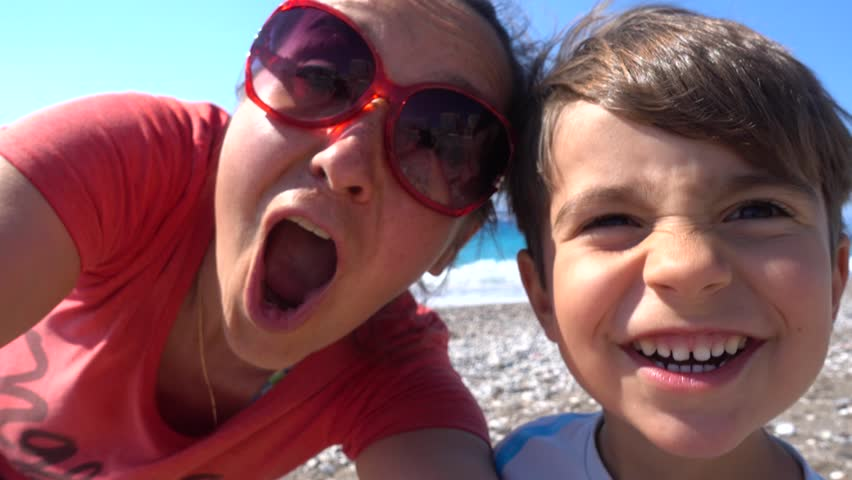 4K Selfie of funny mother and son near the azure sea