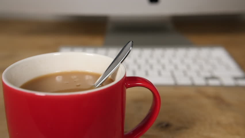 Slow motion stirring with teaspoon cup of tea spinning on computer work desk, cup of hot drink in red mug  | Shutterstock HD Video #1010378507