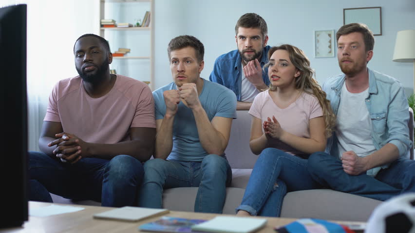 Multi-ethnic group of friends watching football game at home, celebrating goal | Shutterstock HD Video #1010378927