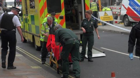 London, United Kingdom (UK) - 05 09 2012: Paramedics wheel covered up dead body on a stretcher towards ambulance