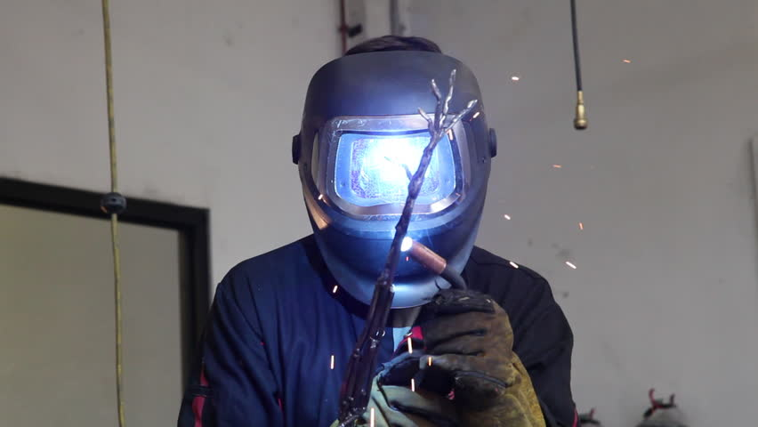Reflections of sparks and light from an arc welder are seen in the faceplate of a man's welding helmet as he works on one limb of a metal armature. | Shutterstock HD Video #1010385467